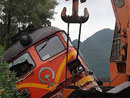 现场救援人员用吊臂把受损列车吊起
