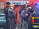 警察在事发地一辆警车旁持枪警戒