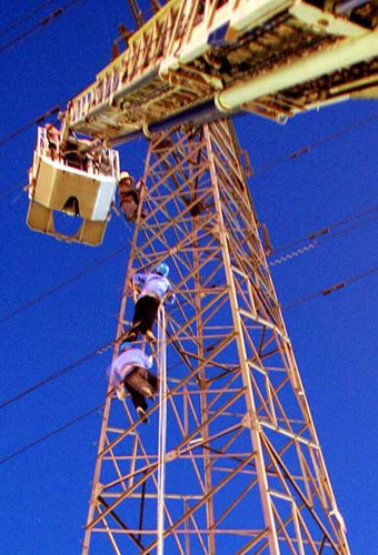 一男子已爬上35米的高压电铁塔